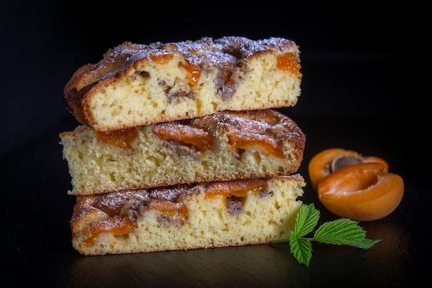 Homemade organiczny deser ciasto morelowe gotowy do spożycia. tarta morelowa z orzechami na czarnym tle, z bliska
