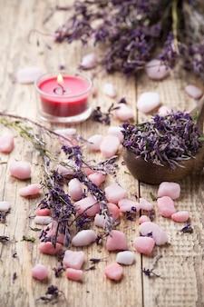 Homeopatyczna sól morska, lawendowe suszone kwiaty i drewniana powierzchnia.