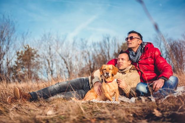 Homoseksualna męska para kłaść na koc w trawie z psem