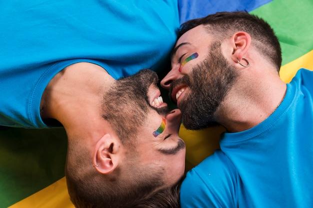 Homoseksualna para kłaść na tęczy flaga