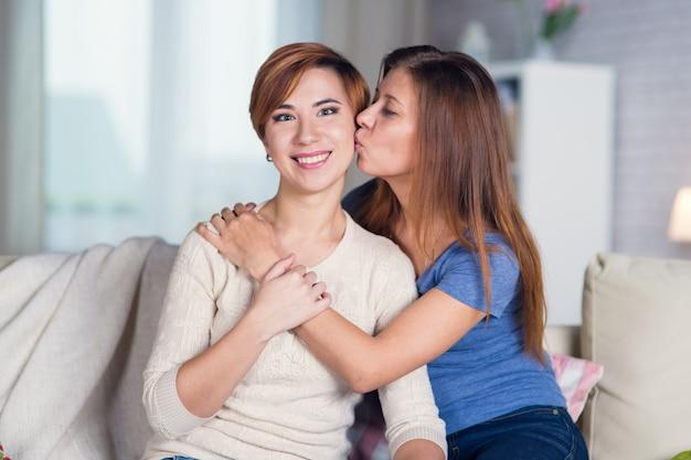 Homoseksualna para lesbijek w domu na kanapie całuje się w policzek przytulając się i ciesząc