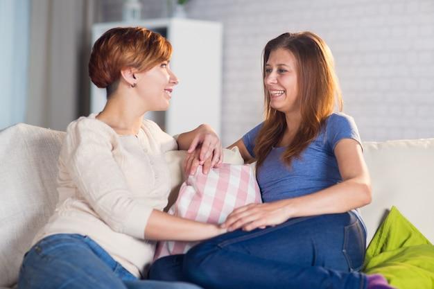 Homoseksualna para lesbijek w domu na kanapie przytula się i cieszy