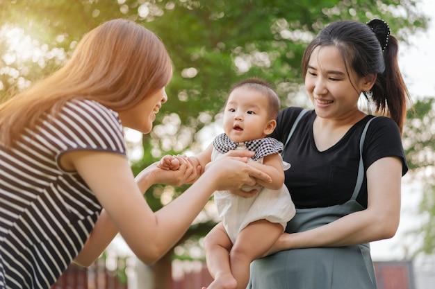 Homoseksualna rodzina matek przytula się i bawi się z dzieckiem na zielonym tle bokeh ze światłem słonecznym