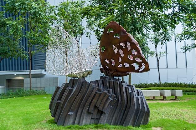Hong kong, chiny 29 stycznia 2016: metalowa rzeźba dwóch białych i brązowych motyli siedzących na skale w parku. rzeźby z hongkongu