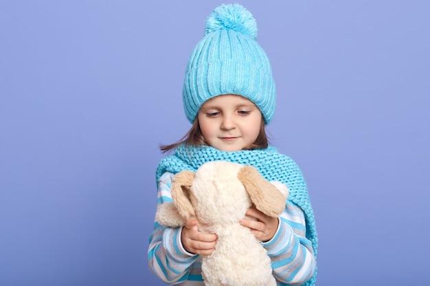 Horizontalshot dziewczynka trzyma w rękach swoją miękką zabawkę dla psa i patrzy na nią
