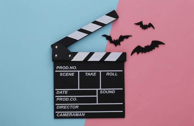 Horror, motyw halloween. klaps filmowy i latające ozdobne nietoperze na różowym niebieskim pastelu