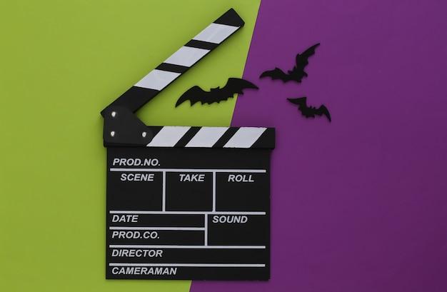 Horror, motyw halloween. klaps filmowy i latające ozdobne nietoperze na zielonofioletowym tle