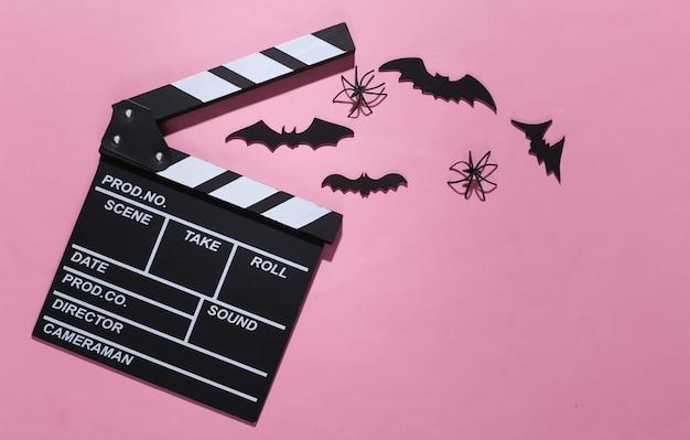Horror, motyw halloween. klaps filmowy i latające ozdobne nietoperze, pająki na różowym jasnym