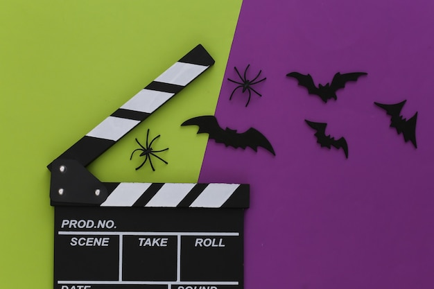 Horror, motyw halloween. klaps filmowy i latające ozdobne nietoperze, pająki na zielonofioletowym tle