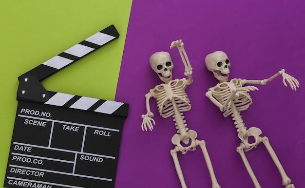 Horror, motyw halloween. klaps filmowy i ozdobne szkielety na zielonofioletowym tle