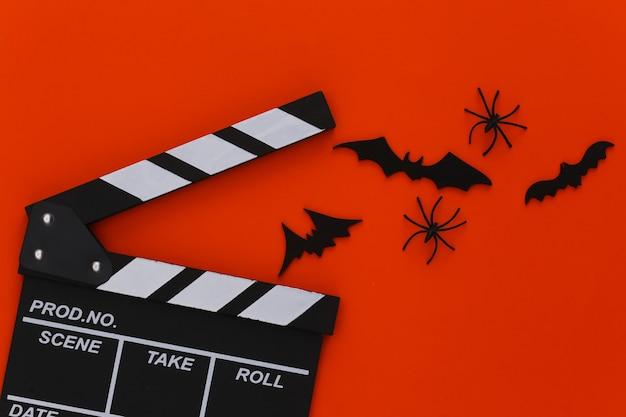 Horror, motyw halloween. klaps filmowy, pająki i latające ozdobne nietoperze na pomarańczowo