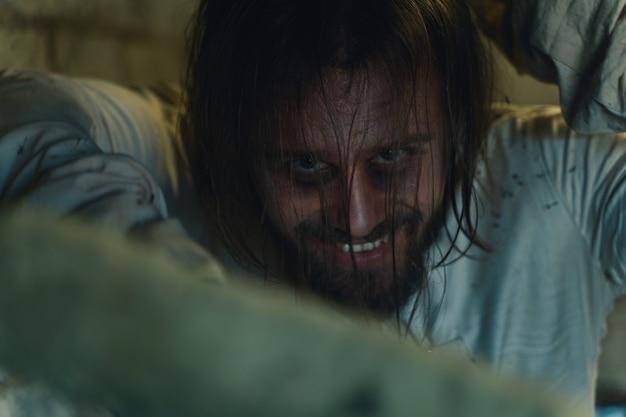Horror na święta halloween szalony mężczyzna w brudnej koszulce pomiarowej w starym zrujnowanym domu jest zamknięty i przeraża wszystkich w pobliżu oczekując ofiary