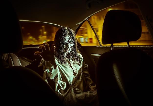 Horror zombie kobieta z zakrwawioną twarzą w samochodzie, nocne miasto