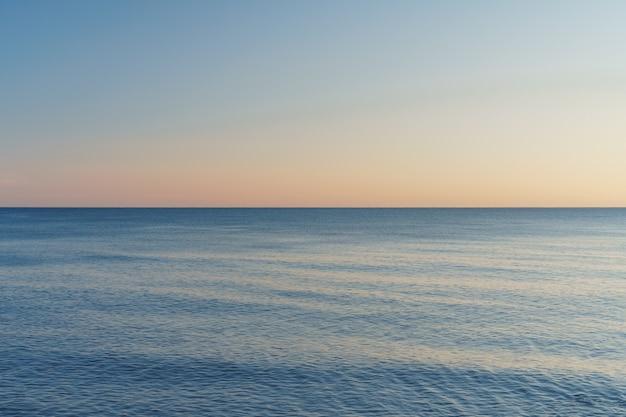 Horyzont dzielący morze i niebo na równe części o zachodzie słońca