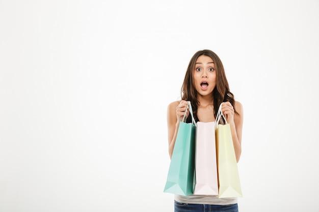 Horyzontalny obrazek pozuje na kamerze z otwartym usta i trzyma udział zakupy paczki zdziwiona kobieta, odizolowywająca nad biel ściany kopii przestrzenią
