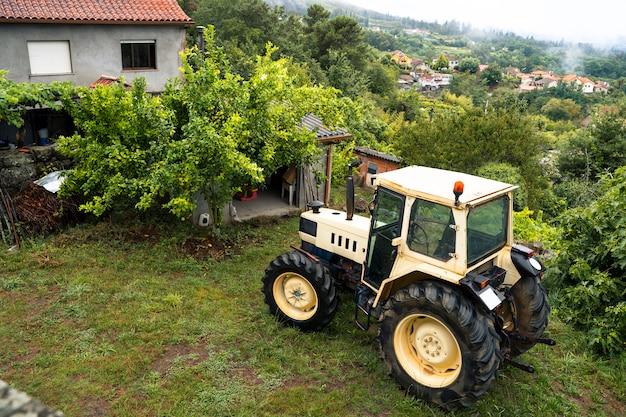 Horyzontalny odgórny widok wieś ciągnik w północy hiszpania, galicia. sezon zimowy. wilgotność i deszczowa pogoda w domu. natura wiejski krajobraz na zieleni polu z nieociosanymi domami.