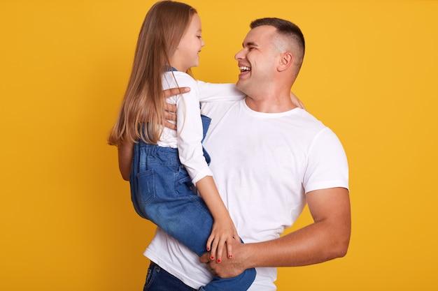 Horyzontalny shotof tata i córka w studiu nad kolorem żółtym
