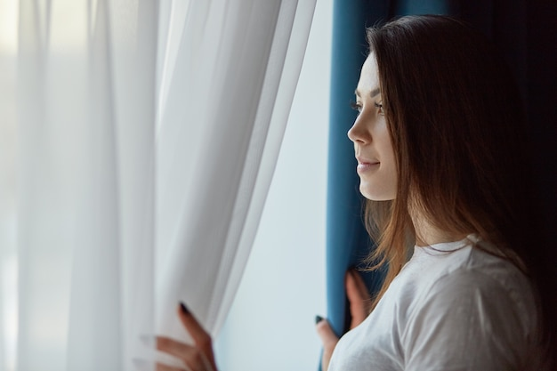 Horyzontalny strzał atrakcyjnej brunetki zadumana młoda kobieta w przypadkowej białej t koszula, patrzeje przez okno z rozważnym wyrażeniem