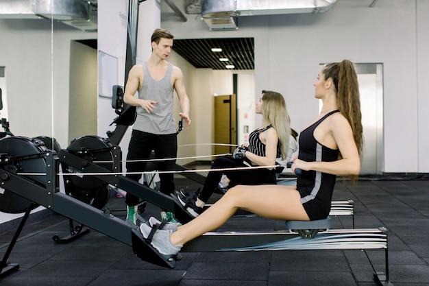 Horyzontalny strzał dwa młodej kobiety atlety ćwiczy przy gym na posadzonej rzędu kabla maszynie. przystojny trener doradzający jak wykonywać ćwiczenia