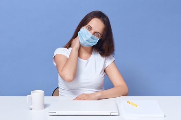 Horyzontalny strzał kobieta pracuje przy laptopem w domu, dama ma dystansową pracę, pozuje przy biurkiem odizolowywającym nad błękitem