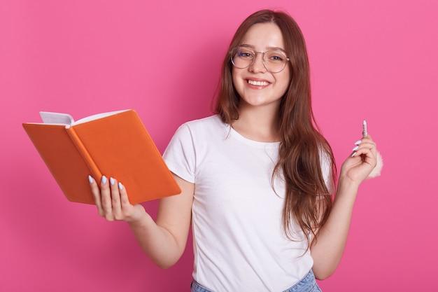 Horyzontalny strzał młoda atrakcyjna caucasian kobieta w białych przypadkowych ubraniach i okularach, trzyma notatnika i penil w rękach