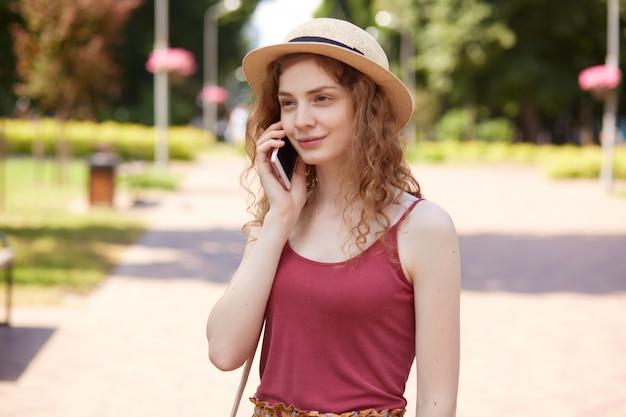 Horyzontalny strzał piękna młoda kobieta w słomianym kapeluszu i bordowym t koszula