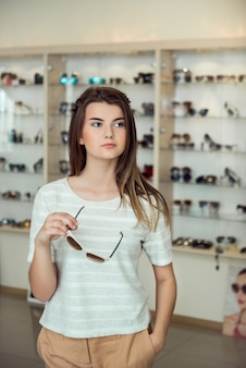 Horyzontalny strzał śliczna kobieta z elegancką fryzury pozycją w okulistycznym sklepie podczas gdy podnoszący okulary przeciwsłonecznych