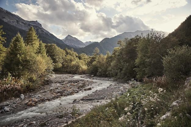 Horyzontalny strzał strumyk st. maria val müstair, engadin, szwajcaria pod chmurnym niebem