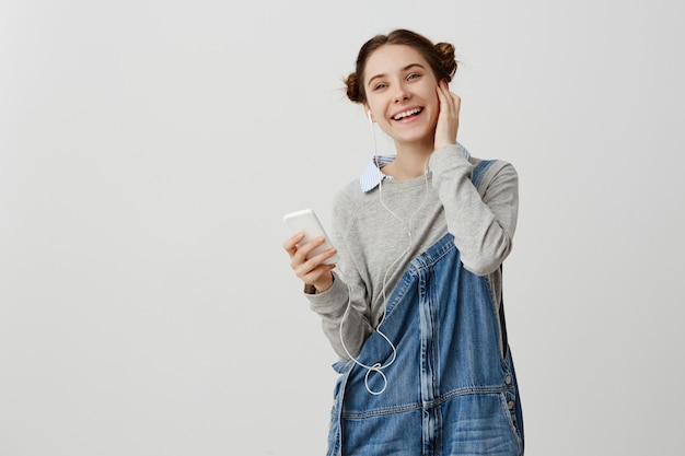 Horyzontalny strzał uradowana kobieta słucha rytmiczną muzykę przez hełmofonów z odango babeczkami. żeński fashionista wyraża szczęście i przyjemność używać mądrze telefon pozuje nad biel ścianą. skopiuj miejsce