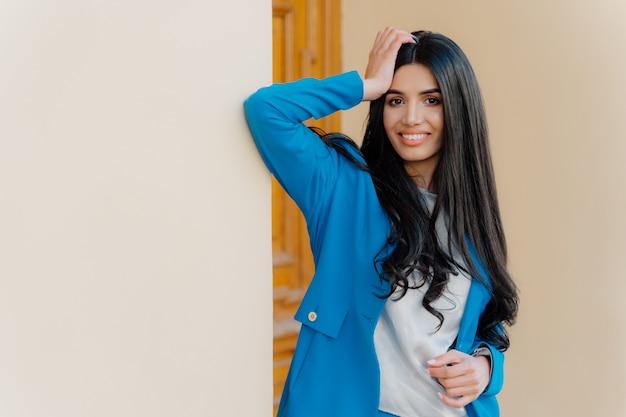 Horyzontalny strzał uśmiechnięta brunetki młoda kobieta utrzymuje jeden rękę na głowie