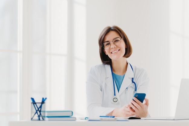 Horyzontalny widok uśmiechnięta profesjonalista lekarka pracuje w klinice, pozuje przy nowożytnym szpitalnym biurem z elektronicznymi gadżetami