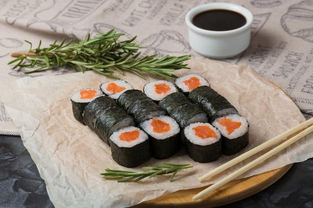Hosomaki stacza się zbliżenie na czarnym talerzu z selekcyjną ostrością. bułki z wodorostami, ryżem, łososiem