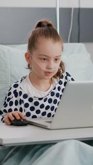 Hospitalizowana chora dziewczyna grająca w gry wideo online za pomocą laptopa