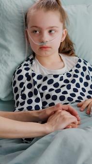 Hospitalizowane dziecko noszące rurkę nosową z tlenem leżące w łóżku z medycznym oksymetrem na palcu