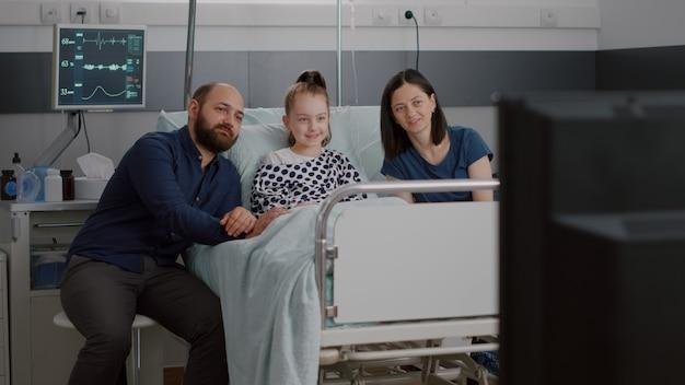 Hospitalizowany chory mały pacjent leżący w łóżku z rodziną oglądając film rozrywkowy w telewizji...