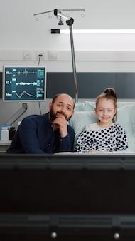 Hospitalizowany chory pacjent odpoczywa w łóżku z rodziną oglądając film animowany w telewizji