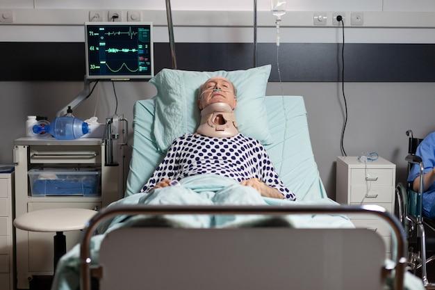 Hospitalizowany senior leżący nieprzytomny w łóżku szpitalnym, noszący kołnierz ortopedyczny, mający poważne obrażenia zdrowotne, oddychający przez maskę tlenową z intensywnym bólem
