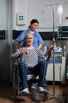 Hospitalizowany starszy mężczyzna siedzący na wózku inwalidzkim w sali szpitalnej, trzymający kroplówkę dożylną z oksymetrem przymocowanym do palca