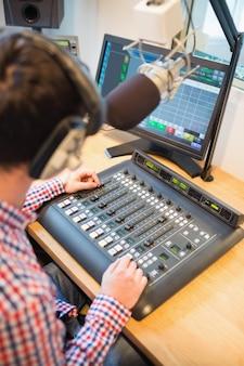 Hosta radiowego używającego miksera dźwięku na stole