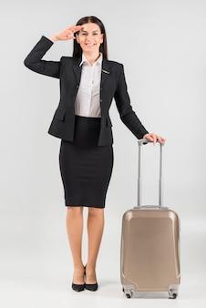 Hostessa w garniturach z bagażem pozdrawiającym