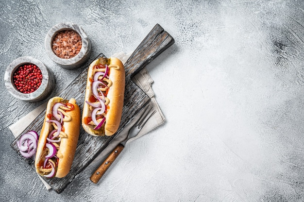 Hot dog wegetariański z dodatkami i bezmięsną kiełbasą. białe tło. widok z góry. skopiuj miejsce.