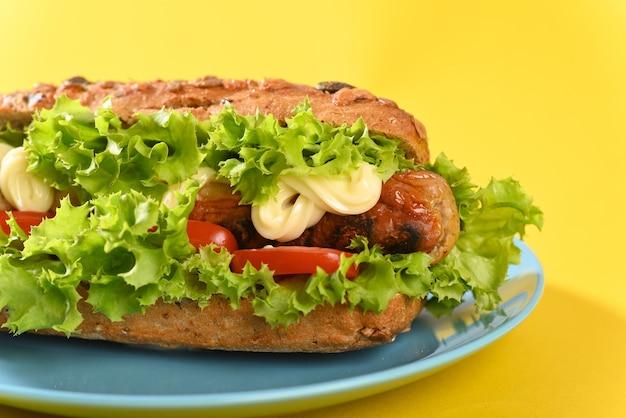 Hot dog z dużą ilością zielonej sałaty i smażonymi kiełbaskami