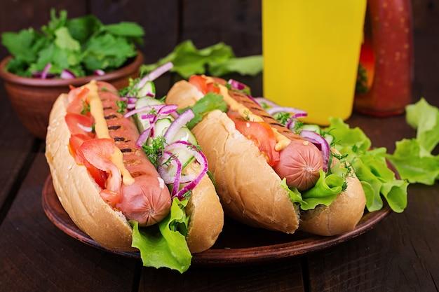 Hot dog z kiełbasą, ogórkiem, pomidorem i sałatą