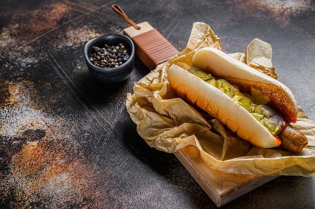 Hot dog z kurczak kiełbasą na drewnianej tnącej desce w kraft papierze, fasta food menu restauracyjny pojęcie. niezdrowe jedzenie.