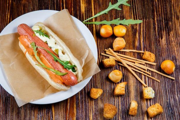 Hot dog z marynatami i rukolą i przekąskami z wędzonego piwa
