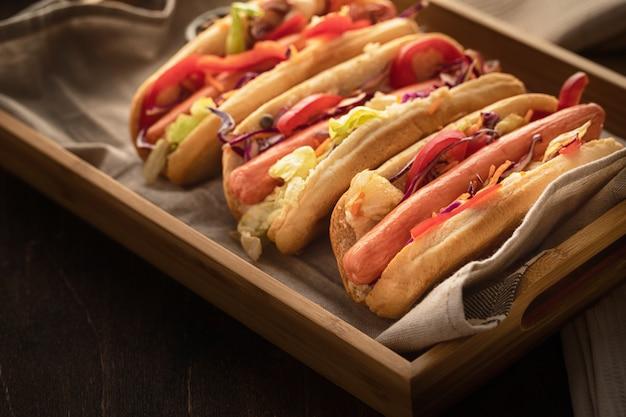 Hot dog z papryką, pomidorem, sałatą i sałatką wymieszać na drewnianym.