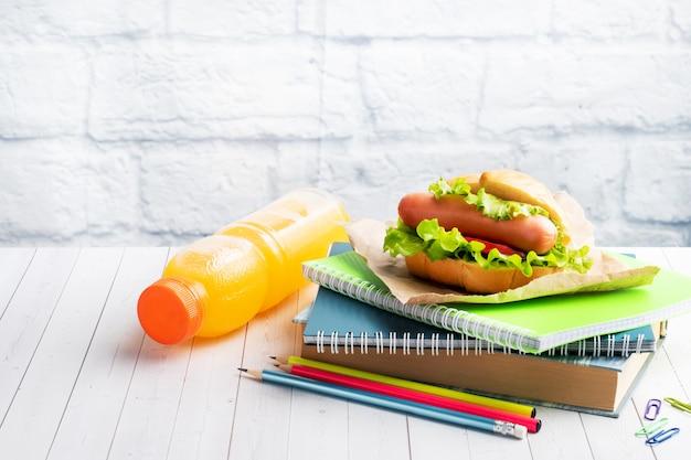 Hot dog z sałatą, pomidorem i kiełbasą. zeszyty i artykuły papiernicze. śniadanie w szkole koncepcyjnej. skopiuj miejsce