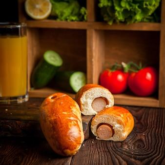 Hot dog z sokiem pomarańczowym i ogórkami oraz pomidorem i sałatą w drewnianej desce