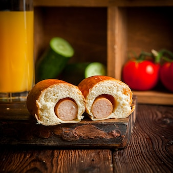 Hot dog z sokiem pomarańczowym, ogórkami i pomidorem w drewnianej desce