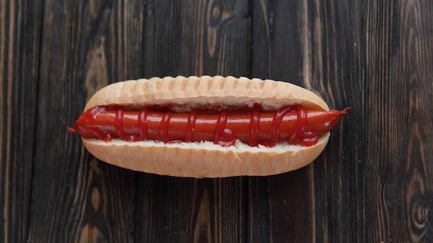 Hot dog z wędzoną kiełbasą na ciemnym drewnianym tlephoto z miejscem na kopię